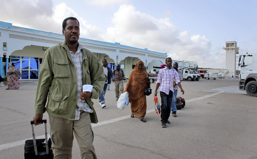 In this photo taken Friday, June 8, 2012, Abdikhafar Abubakar prepares to board a plane back to Minneapolis after returning to Mogadishu to visit his mother for the first time in decades, at the airport in Mogadishu, Somalia. The seaside Somali capital is enjoying a peace that, except for the infrequent attack, has lasted the better part of a year and Somalis who fled decades of war are coming back, as are U.N. workers who long operated out of Nairobi, the capital of neighboring Kenya. (AP Photo/Jason Straziuso)