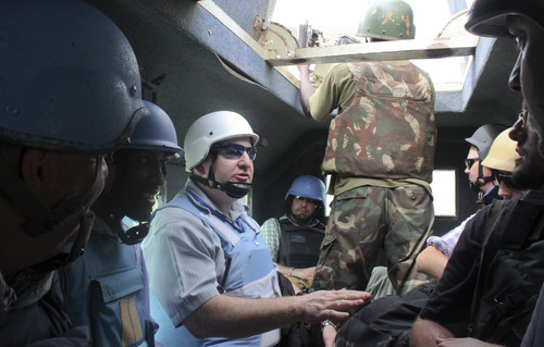 In this photo taken Tuesday, June 5, 2012, Justin Brady, Head of Office for the United Nations Office for the Coordination of Humanitarian Affairs (OCHA) and the first country director of a UN agency to relocate to Somalia, rides in an African Union armored personnel carrier in Mogadishu, Somalia. The seaside Somali capital is enjoying a peace that, except for the infrequent attack, has lasted the better part of a year and Somalis who fled decades of war are coming back, as are U.N. workers who long operated out of Nairobi, the capital of neighboring Kenya. (AP Photo/Jason Straziuso)