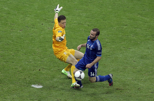Poland goalkeeper Wojciech Szczesny, left, brings down Greece's Dimitris Salpigidis, right, for a penalty during the Euro 2012 soccer championship Group A match between Poland and Greece in Warsaw, Poland, Friday, June 8, 2012. (AP Photo/Gero Breloer)
