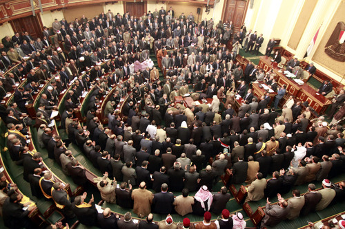 FILE - In this Monday, Jan. 23, 2012 file photo, members of parliament stand and pray for the souls of the victims who died during the uprising that ousted President Hosni Mubarak during the first Egyptian parliament session after the revolution, in Cairo, Egypt. Egypt's highest court has ordered the country's Islamist-dominated parliament dissolved, saying its election about six months ago was unconstitutional. The Supreme constitutional Court ruled Thursday that a third of the legislature was elected illegally. As a result, it says in its explanation of the ruling,
