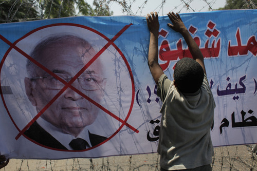 An Egyptian youth hangs a banner with a defaced picture of presidential candidate, Ahmed Shafiq and Arabic that reads