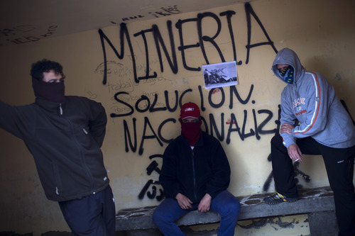 Masked miners stand next to graffiti reading in Spanish