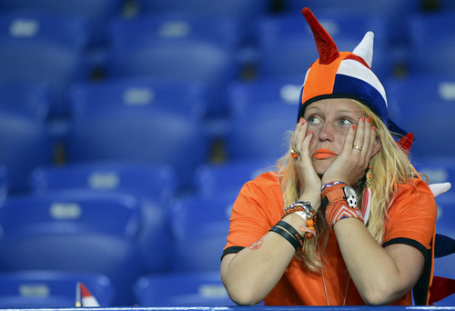 A Dutch fan sits dejected after the Euro 2012 soccer championship Group B match between the Netherlands and Germany in Kharkiv, Ukraine, Wednesday, June 13, 2012. The Netherlands lost the match 1-2. (AP Photo/Geert Vanden Wijngaert)