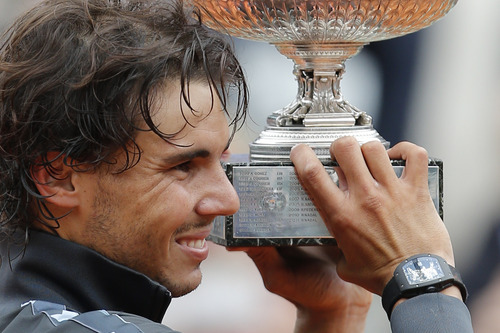 Rafael Nadal of Spain holds the trophy with the inscription of his six previous titles after winning the mens final match against Novak Djokovic of Serbia at the French Open tennis tournament in Roland Garros stadium in Paris, Monday June 11, 2012. Rain suspended the final making it the first French Open not to end on Sunday since 1973. Nadal clinched his seventh title in four sets 6-4, 6-3, 2-6, 7-5, passing Sweden's Bjorn Borg as the all-time record-holder for French Open titles. (AP Photo/Christophe Ena)