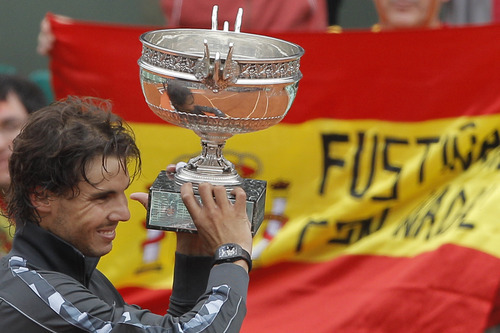The Spanish flag is seen in the background as Rafael Nadal of Spain holds the trophy after winning the mens final match against Novak Djokovic of Serbia at the French Open tennis tournament in Roland Garros stadium in Paris, Monday June 11, 2012. Rain suspended the final making it the first French Open not to end on Sunday since 1973. Nadal won in four sets 6-4, 6-3, 2-6, 7-5, passing Sweden's Bjorn Borg as the all-time record-holder for French Open titles. (AP Photo/Michel Spingler)