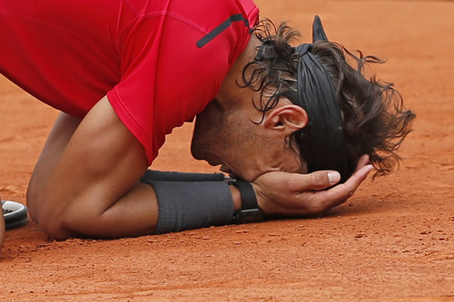 Rafael Nadal of Spain celebrates winning the mens final match against Novak Djokovic of Serbia at the French Open tennis tournament in Roland Garros stadium in Paris, Monday June 11, 2012. Rain suspended the final making it the first French Open not to end on Sunday since 1973. Nadal won in four sets 6-4, 6-3, 2-6, 7-5, passing Sweden's Bjorn Borg as the all-time record-holder for French Open titles. (AP Photo/Bernat Armangue)
