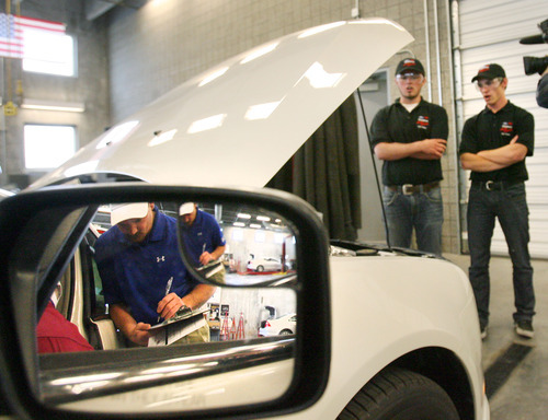 Steve Griffin  |  The Salt Lake Tribune Riverton High School students Jordan Kearns and Chandler Adkins stand next to a Ford Fusion as their work is judged during the Ford/AAA Student Auto Skills Competition at the Salt Lake Community College MIller Campus in Sandy on April 26, 2012. After winning the state competition, they competed and placed fourth at the recent national competition.