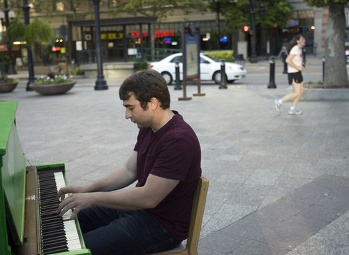 Kim Raff | The Salt Lake Tribune Doug Vandegrift plays a piano installed at the Gallivan Center downtown as part of Utah Museum of Contemporary Art's