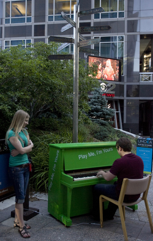 Kim Raff | The Salt Lake Tribune Erin Page watches as Doug Vandegrift plays a piano installed at the Gallivan Center downtown as part of Utah Museum of Contemporary Art's