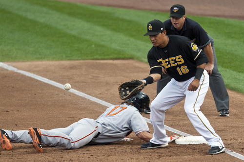 Chris Detrick  |  The Salt Lake Tribune Fresno Grizzlies Charlie Culberson dives safely back to first base past Salt Lake Bees Efren Navarro during the game at Spring Mobile Ballpark Friday June 15, 2012.