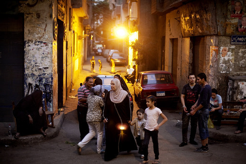 Neighborhood residents outside a polling station in the Abdeen neighborhood of Cairo, Egypt, Sunday, June 17, 2012. For some Egyptians waiting on Sunday in sweltering heat to vote on the second day of presidential elections, their choice has been rendered essentially meaningless with the military poised to hold onto the lion's share of power no matter who wins. (AP Photo/Pete Muller)
