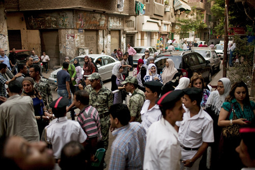 Crowds mass outside a polling center in the Abdeen neighborhood of Cairo, Egypt, Sunday, June 17, 2012. As are set to close at 10 pm, larger numbers of voters are arriving to cast ballots. Egyptians are choosing on Sunday between a conservative Islamist and Hosni Mubarak's ex-prime minister in the second day of a presidential runoff that has been overshadowed by questions on whether the ruling military will transfer power to civilian authority by July 1 as promised. (AP Photo/Pete Muller)