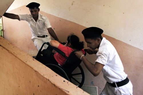 Two Egyptian policemen help a disabled woman in a wheelchair out of a polling station after she voted during the second day of the presidential runoff in Cairo, Egypt Sunday, June 17, 2012. Egyptians are choosing between a conservative Islamist and Hosni Mubarak's ex-prime minister in a second day of a presidential runoff that has been overshadowed by the domination of the country's military. (AP Photo/Nasser Nasser)