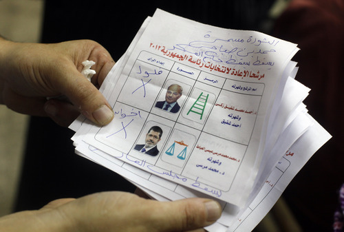 An Egyptian elections official holds unusable ballots at a polling center after the second day of the presidential runoff, in Cairo, Egypt, Sunday, June 17, 2012. As Egyptians voted in a second day of elections for a successor to Hosni Mubarak, the ruling military issued an interim constitution Sunday defining the new president's authorities, a move that sharpened the confrontation with the Muslim Brotherhood and showed how the generals will maintain the lion's share of power no matter who wins. The Arabic handwriting from top to bottom reads