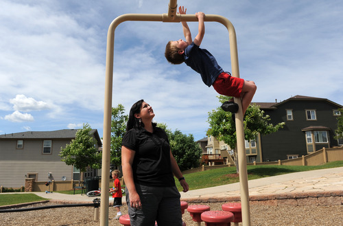 Anne Eliason, left, watches her son Isaac, 5, play at a neighborhood park in Highlands Ranch, Colo., on Monday, June 4, 2012. Isaac has been diagnosed with autism and his family moved from Utah to Colorado because of the insurance options and the superior therapeutic and support services for Isaac. Isaac has appointments nearly everyday to work on speech, occupational and behavioral therapy. Photo by Chris Schneider
