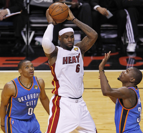 Miami Heat small forward LeBron James (6) passes between Oklahoma City Thunder point guard Russell Westbrook and Kevin Durant, during the first half at Game 3 of the NBA Finals basketball series, Sunday, June 17, 2012, in Miami. (AP Photo/Wilfredo Lee)