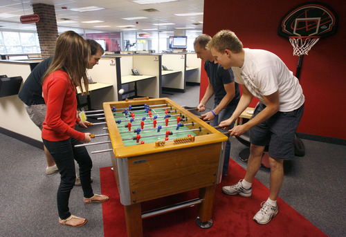 Francisco Kjolseth  |  The Salt Lake Tribune Taking a break from work, Jennifer Brinkerhoff, Karl Hite, James Raynor and Caleb Cox, from left, battle it out on one of the foosball tables in the hip space of software company Qualtrics in Provo. The company which makes online survey software recently got $70 million in first round venture capital and are a hot company growing in Utah county.