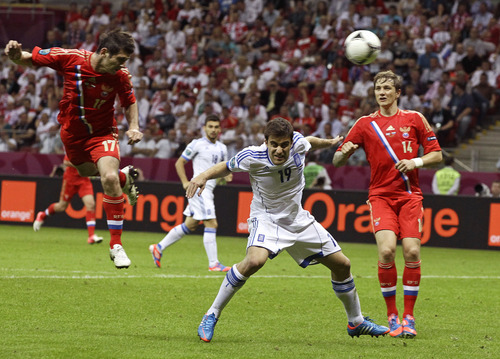 Russia's Alan Dzagoyev, left, heads the ball during the Euro 2012 soccer championship Group A  match between Greece and Russia in Warsaw, Poland, Sunday, June 17, 2012. (AP Photo/Sergey Ponomarev)