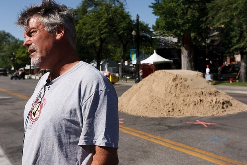 Trent Nelson  |  The Salt Lake Tribune Artist Ted Siebert stands next to 20 tons of sand that was dumped on Library Square on June 19 for a sand sculpture he's creating as part of the Utah Arts Festival in Salt Lake City.
