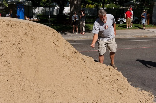 Trent Nelson  |  The Salt Lake Tribune Artist Ted Siebert checks the texture of the twenty tons of sand that was dumped on June 19 for a sand sculpture he is creating as part of the Utah Arts Festival in Salt Lake City.