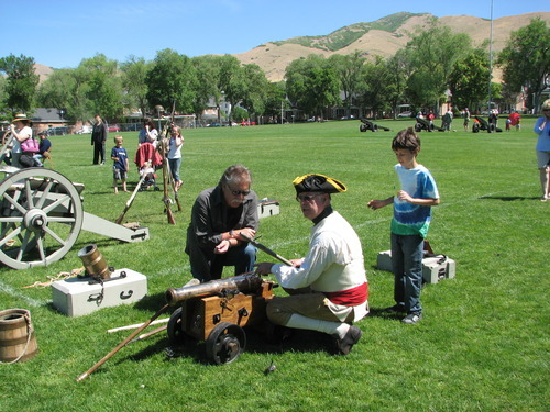 Courtesy photo Dressed in a Revolutionary War uniform, Cap Cresap of California shows Robert Kirby how to fire a 2-pound cannon typical of those used during the Revolutionary War. The pair were at Fort Douglas in Salt Lake City on Saturday.