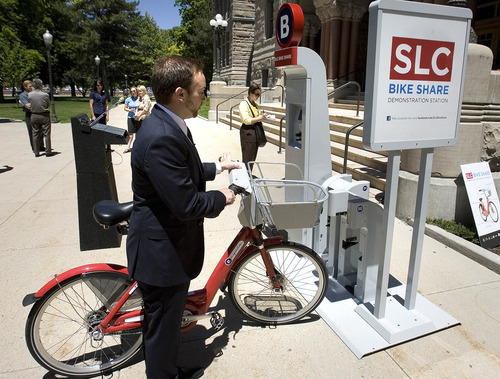Paul Fraughton | The Salt Lake Tribune Ben Bolte, bike share project manager, demonstrates how to use a bike-share station on Tuesday, June 19, 2012. The Salt Lake City program expects to kick into gear in March 2013.