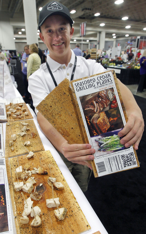 Al Hartmann  |  The Salt Lake Tribune Jaxon McAffee offers chicken samples barbequed on Gourmet Seasoned Grilling Planks at the Associated Food Stores Food Show 2012 at the Salt Palace Convention Center Wednesday June 20.  Wasatch Mountain Plank is a Highland Utah company that makes six different cedar seasoned planks with everything from Chili Lime Chipotli to Rosemary Merlot flavors for the home barbequer.   The food show includes Utah grown and manufactured products to be seen by  400 grocers doing business in eight states.