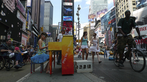 Courtesy UMOCA A girl plays a piano in New York's Times Square, as part of British artist Luke Jerram's