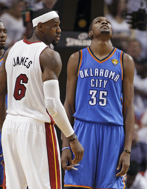 Miami Heat small forward LeBron James (6) and Oklahoma City Thunder small forward Kevin Durant pause between plays during the second half at Game 4 of the NBA Finals basketball series, Tuesday, June 19, 2012, in Miami.  (AP Photo/Lynne Sladky)