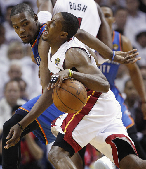 Miami Heat point guard Mario Chalmers (15) drives around Oklahoma City Thunder small forward Kevin Durant (35) during the second half at Game 4 of the NBA Finals basketball series, Tuesday, June 19, 2012, in Miami.  (AP Photo/Lynne Sladky)