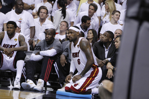 Miami Heat small forward LeBron James (6) kneels on the sideline after taking a spill against the Oklahoma City Thunder during the second half at Game 4 of the NBA finals basketball series, Tuesday, June 19, 2012, in Miami.  (AP Photo/Lynne Sladky)