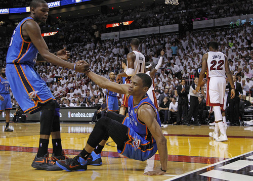 Oklahoma City Thunder small forward Kevin Durant (35) helps point guard Russell Westbrook up during the second half at Game 4 of the NBA finals basketball series against the Miami Heat, Tuesday, June 19, 2012, in Miami.  (AP Photo/Lynne Sladky)