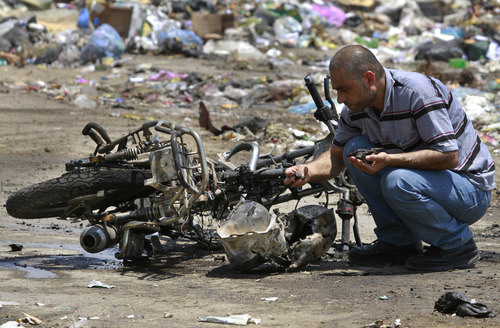 A Palestinian inspects the debris of a destroyed motorcycle after an Israeli airstrike in Beit Hanoun, northern Gaza Strip, Monday, June 18 2012. Militants crossed from Egypt's turbulent Sinai Peninsula into southern Israel on Monday and opened fire on civilians building a border security fence, defense officials said. One of the Israeli workers was killed, and two assailants died in a gunbattle with Israeli troops responding to the attack. Several hours after the attack, an Israeli airstrike killed two men riding a motorcycle in the northern Gaza Strip near the Israeli border. The Islamic Jihad militant group said the men were members on a