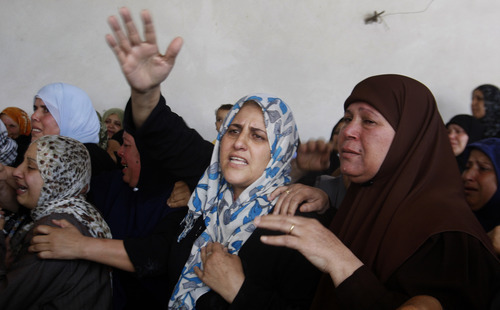 Palestinian women mourn during the funeral of Islamic Jihad militants Mohammed Shabat and Ismail Abu Odeh in Beit Hanoun, northern Gaza Strip, Monday, June 18, 2012. Militants crossed from Egypt's turbulent Sinai Peninsula into southern Israel on Monday and opened fire on civilians building a border security fence, defense officials said. One of the Israeli workers was killed, and two assailants died in a gunbattle with Israeli troops responding to the attack. Several hours after the attack, an Israeli airstrike killed two men riding a motorcycle in the northern Gaza Strip near the Israeli border. The Islamic Jihad militant group said the men were members on a