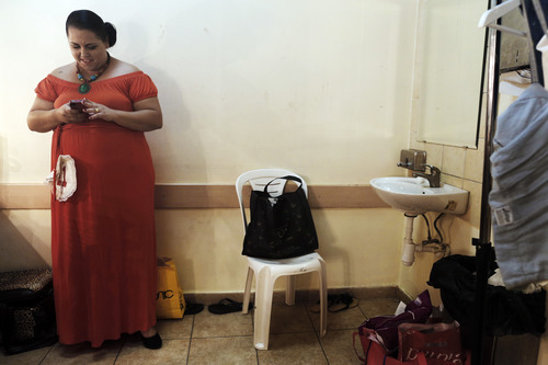 In this Monday, June 18, 2012 photo, a contender for the Israeli 2012 fat beauty queen contest, waits backstage before walking during the show, in the southern city of Beersheba, Israel. In order to participate, contestants are required to weigh over 80 kilograms (176 pounds). (AP Photo/Tsafrir Abayov)