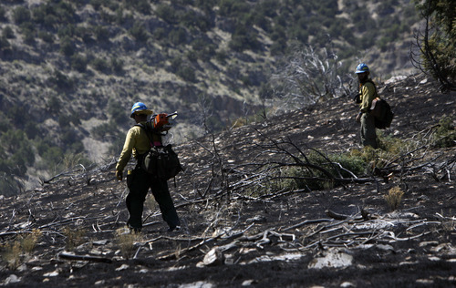 Francisco Kjolseth  |  The Salt Lake Tribune Fire fighters Harrison Long, left, and Joe Williams, work work to wrap up the nearly 1700 acres that has burned south of Saratoga Springs along Lake Mountain that is 20 percent contained as of Friday, April 1, 2012. The fire which began on Thursday afternoon is under investigation and is suspected to have started by two people discharging firearms against the hillside. The sheriffs office has closed the hillside from Pelican Point to Clyde Knoll in the meantime.