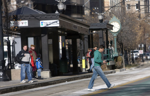 Al Hartmann  |  Tribune file photo A pedestrian crosses Main Street and train tracks mid-block at the Gallivan TRAX station near 300 South in Salt Lake City. The Utah Transit Authority will start writing tickets for