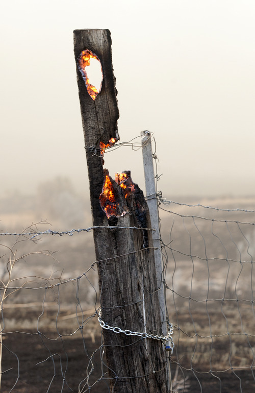 Christopher Reeves  |  Special to The Salt Lake Tribune  A fence post burns near Saratoga Springs on Friday, June 22, 2012.
