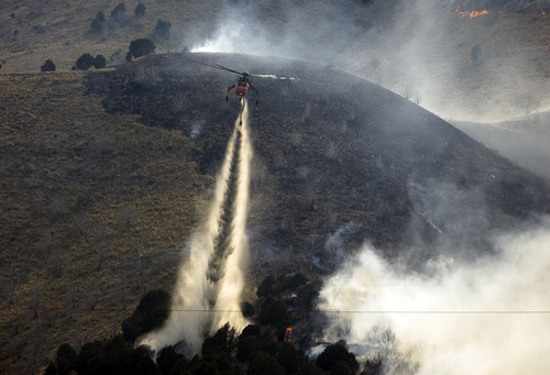 Kim Raff  |  The Salt Lake Tribune Helicopters are used to try and contain the Dump Wildfire in Saratoga Springs-Eagle Mountain area in Saratoga Springs, Utah on June 22, 2012.