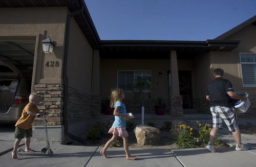 Kim Raff | The Salt Lake Tribune (right) Jared Hobbs and his children (left) Porter and Tylee Hobbs unpack their vehicle upon returning to their home in the Jacob Ranch subdivision after being evacuated due to the Dump Wildfire in Saratoga Springs, Utah on June 23, 2012.