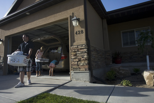 Kim Raff | The Salt Lake Tribune Jared Hobbs and his family unpack their vehicle upon returning to their home in the Jacob Ranch subdivision after being evacuated due to the Dump Wildfire in Saratoga Springs, Utah on June 23, 2012.