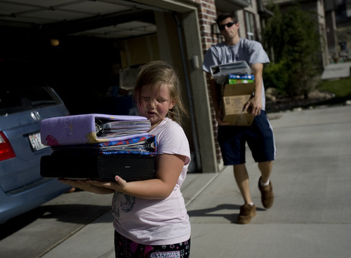 Kim Raff | The Salt Lake Tribune Amara Derington and her uncle John Derington bring in family scrapbooks after being able to return to their home after being evacuated due to the Dump Wildfire in the Saratoga Hills subdivision in Saratoga Springs, Utah on June 23, 2012.