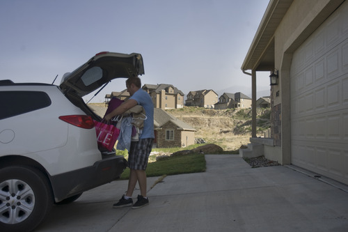 Kim Raff | The Salt Lake Tribune Sean McKenna, an evacuated residents due to the Dump Wildfire, returns to his home and unpacks his car in the Saratoga Hills subdivision in Saratoga Springs, Utah on June 23, 2012.