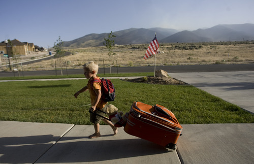 Kim Raff | The Salt Lake Tribune With a back drop of still smoky mountains, Porter Hobbs helps his family unpack their vehicle upon returning to their home in the Jacobs Ranch subdivision after being evacuated due to the Dump Wildfire in Saratoga Springs on June 23, 2012.