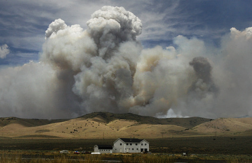 Scott Sommerdorf  |  The Salt Lake Tribune              A farmhouse just off Hwy 132 near Fountain Green is dwarfed by a huge cloud of smoke caused by the brush fire near there, Sunday, June 24, 2012.