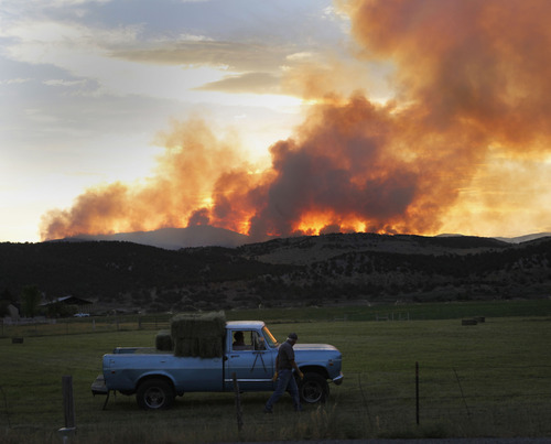 Al Hartmann  |  The Salt Lake Tribune   Farmer north of Mount Pleasant on Highway 89 keeps working in his alfalfa field past sunset as the Wood Hollow fire keeps burning in the mountains several miles to the northwest.