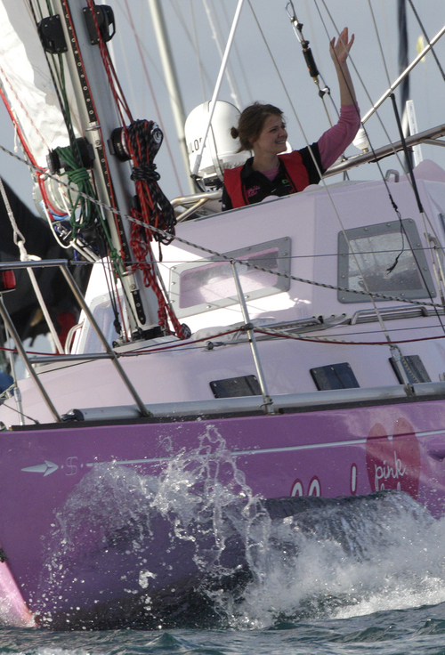 Sixteen-year-old Jessica Watson waves as she sails past the finish line at the entrance to Sydney Harbour in Sydney, Australia, Saturday, May 15, 2010, capping off a nearly 23,000 nautical miles voyage. Watson crossed the finish line of her round-the-world journey Saturday, becoming the youngest person to sail solo, nonstop and unassisted around the world. (AP Photo/Rob Griffith)