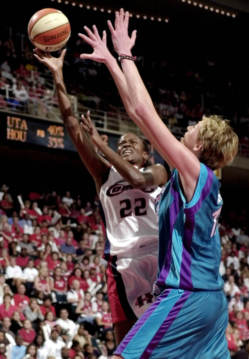 Houston Comets forward Sheryl Swoopes (22) goes to the basket guarded by Utah Starzz center Margo Dydek (12) in the first half of their WNBA playoff game Tuesday, Aug. 20, 2002, in Houston. (AP Photo/Pat Sullivan)