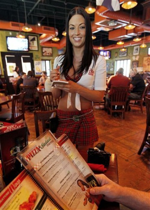 In this May 16, 2012 photo, Ashley Carpenter takes lunch orders at the Tilted Kilt, in Tempe, Ariz. The Tilted Kilt is part of a booming niche in the beleaguered restaurant industry known as