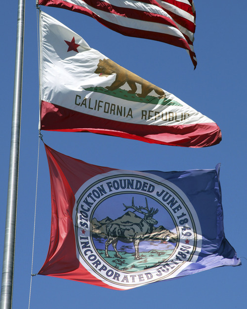 The flag of Stockton, Calif., flies beneath the California Republic flag near city hall Tuesday, June 26, 2012, in Stockton, Calif. Stockton officials continue to grapple with the city's financial plight, struggling to restructure millions of dollars of debt threatening to turn the city with the nation's second highest foreclosure rate into the largest American city to file for bankruptcy. (AP Photo/Ben Margot)